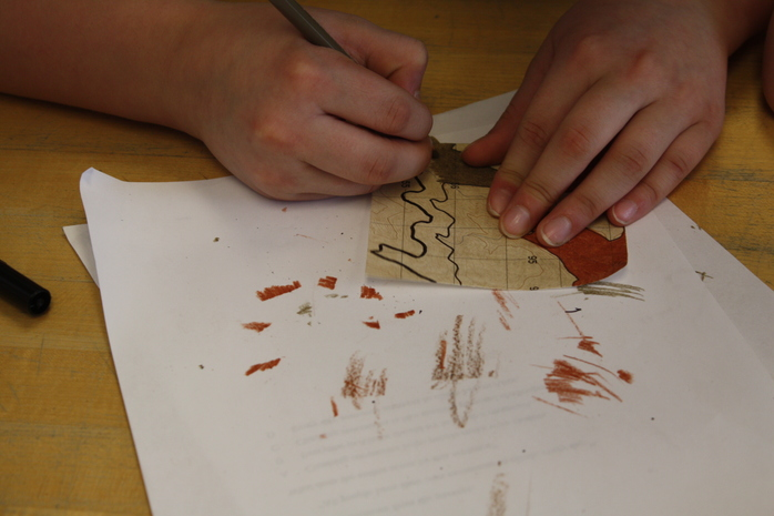 A student drawing on a topo chart square.
